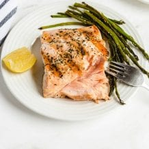 close up shot of grilled salmon on a plate with asparagus and a slice of lemon