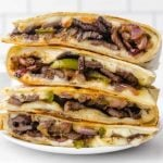 close up shot of steak quesadilla recipe stacked on top of each other on a plate
