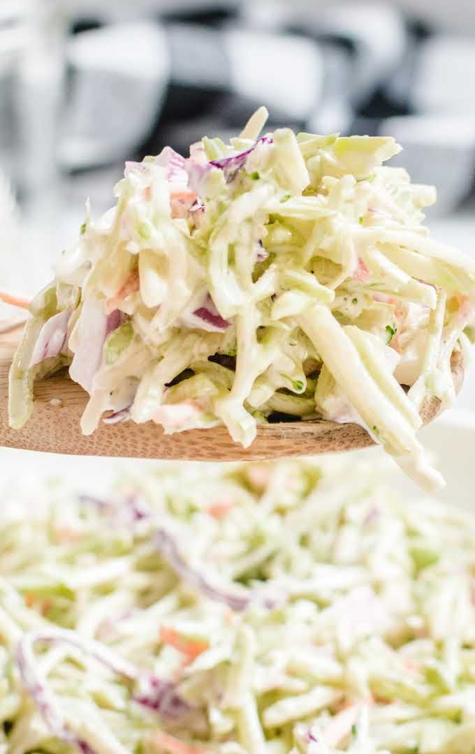 close up shot of a piece of broccoli slaw being picked up from a bowl with a wooden spoon