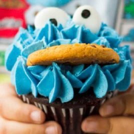 close up shot of Cookie Monster Cupcakes with candy eyes and a cookie being held