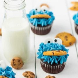 close up shot of Cookie Monster Cupcakes with a jug of milk