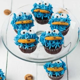 close up shot of Cookie Monster Cupcakes with candy eyes and a cookie on a clear serving stand