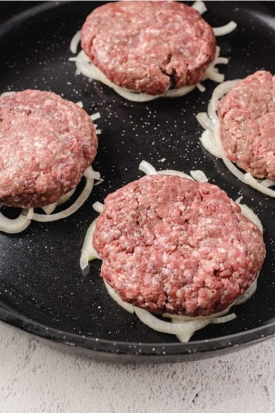 close up shot of uncooked Oklahoma Fried Onion Burgers over sliced onions in a skillet