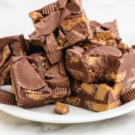 close up shot of slices of Reese's peanut butter fudge stacked on top of each other on a white plate