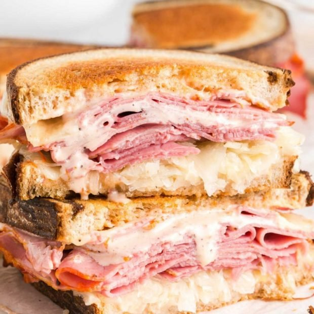 close up shot of Reuben Sandwich stacked on top of each other on a wooden board