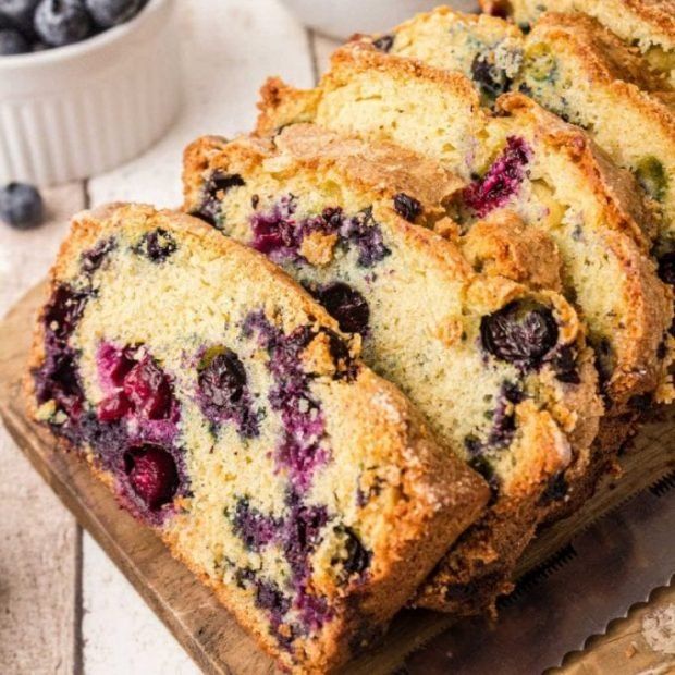 close up shot of slices of blueberry bread on a wooden serving board