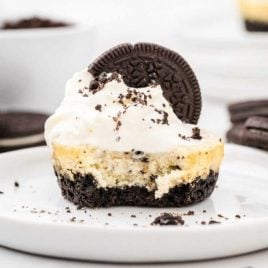 cookies and cream cheesecakes with a Oreo cookie on top on a plate with a piece taken out of it