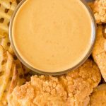overhead shot of copycat chick fil a sauce in a condiment bowl with chicken tenders and fries