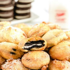 close up shot of deep fried oreos stacked on top of each other on a plate sprinkled with powdered sugar