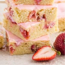 close up shot of strawberry lemon blondies with strawberry glaze stacked on top of each other