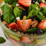 close up shot of strawberry spinach salad garnished with feta cheese in a bowl