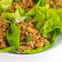 close up shot of Asian chicken lettuce wrap garnished with green onions on a plate