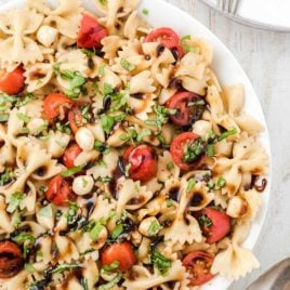 close up overhead shot of Caprese pasta salad topped with balsamic glaze and basil in a bowl