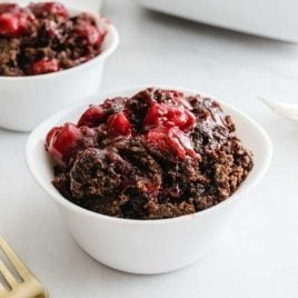 a serving of chocolate cherry dump cake in a white bowl