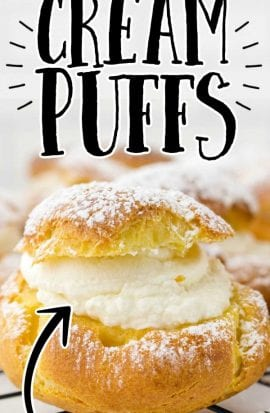 close up shot of cream puffs sprinkled with powdered sugar on a cooling rack
