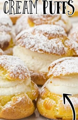 close up shot of cream puffs sprinkled with powdered sugar on a plate