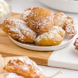 close up shot of Funnel cake bites topped with powdered sugar on a plate