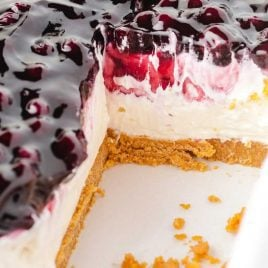 close up shot of No Bake Blueberry Cheesecake in a pan with a slice missing