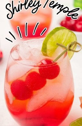 close up shot of a glass of Shirley Temple garnished with cherries and a lime slice