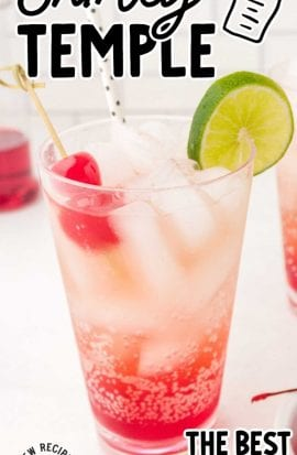 close up shot of a glass of Shirley Temple garnished with cherries, a lime slice, and a straw
