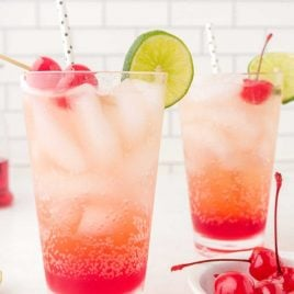 close up shot of glasses of Shirley Temple garnished with cherries, lime slices, and a straw