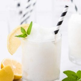 close up shot of alcoholic frozen lemonade in a clear glass with a slice of lemon and mint served with a straw