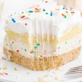 close up shot of birthday cake delight with sprinkles on top on a white plate