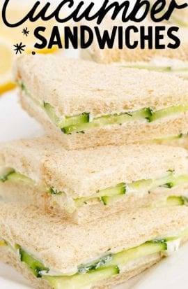 close up shot of cucumber sandwiches piled on top of each other on a plate