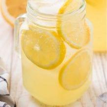 close up shot of hard lemonade in a glass jar with slices of lemon