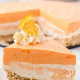 close up shot of a slice of no-bake orange creamsicle cheesecake on a plate