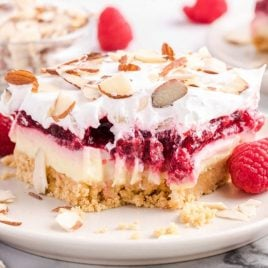 close up shot of raspberry lasagna with almonds on a plate