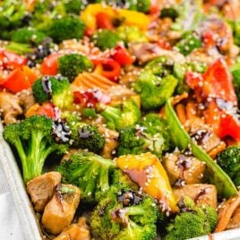 close up shot of sheet pan stir fry topped with sesame seeds and sauce in a sheet pan