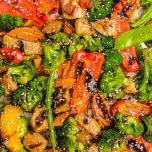 close up overhead shot of sheet pan stir fry topped with sesame seeds and sauce