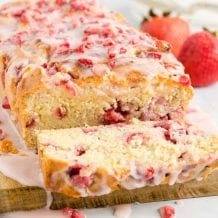 close up shot of a loaf of strawberry bread with strawberries and glaze on top with a slice cut off on a wooden board