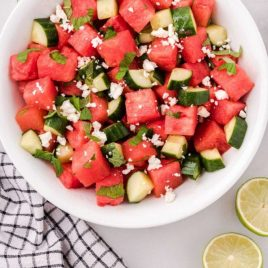 close up overhead shot of a serving of watermelon salad topped with mint leaves and feta cheese in a bowl