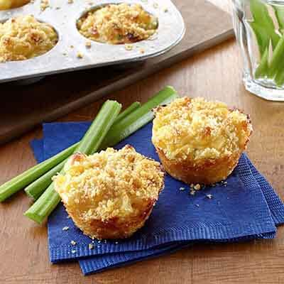 mini mac and cheese made in a muffin pan sitting on a blue napkin with celery sticks