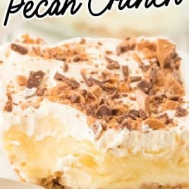 close up shot of a slice of butter pecan crunch topped with cool whip and crumbled heath candy bars on a plate
