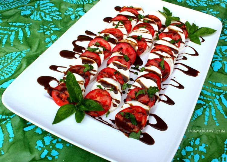 white square plate with mozzarella cheese, tomatoes, basil and glaze drizzled on top