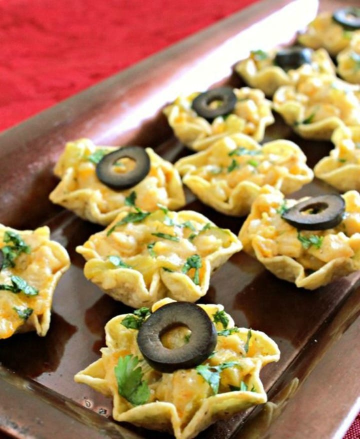 little corn chip cups filled with chicken nacho filling and topped with a sliced black olive