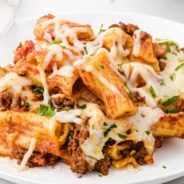 close up shot of a serving of Crockpot Baked Ziti on a plate with a fork