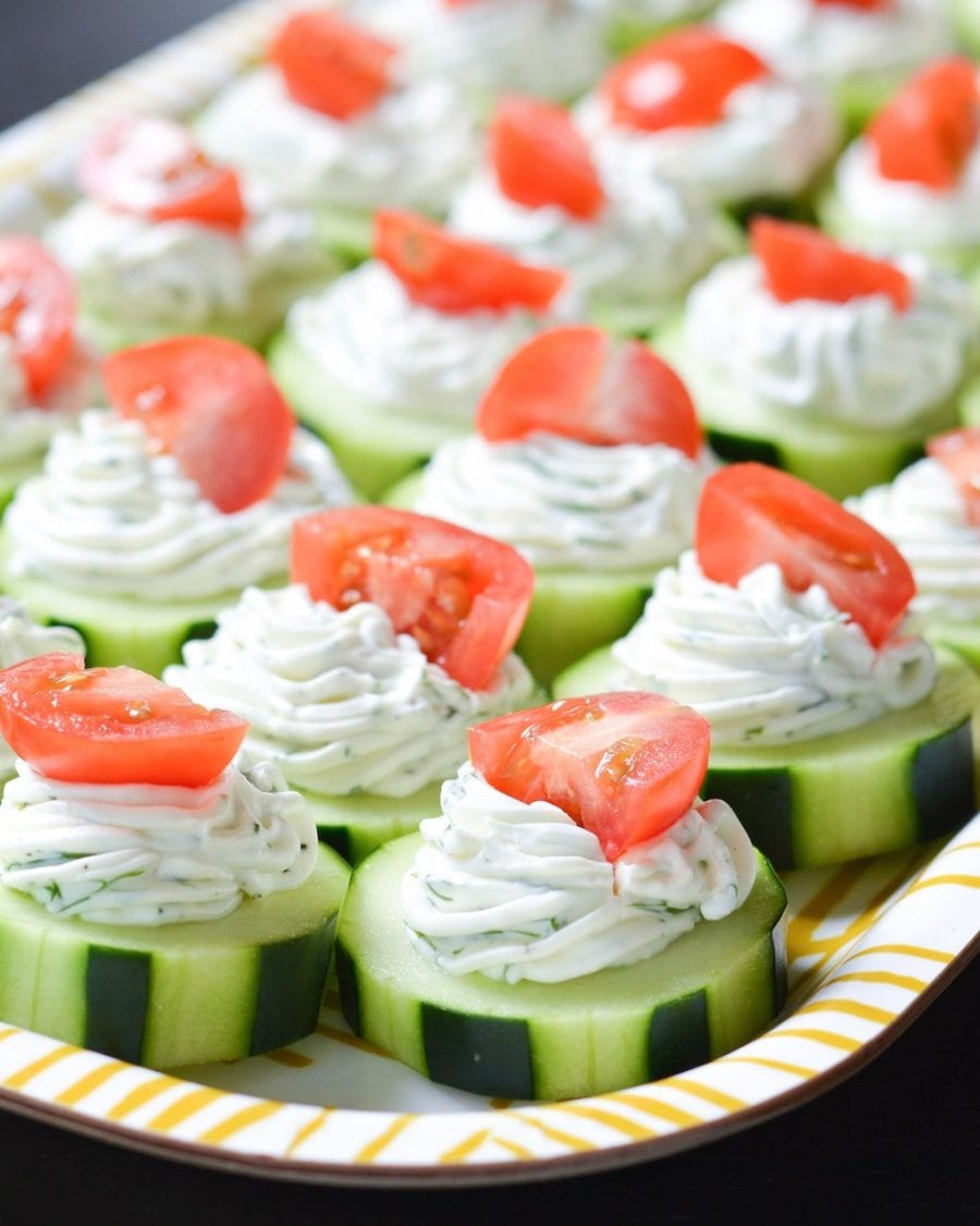 topped with a dill cream cheese mixture and topped with a piece of a cherry tomato