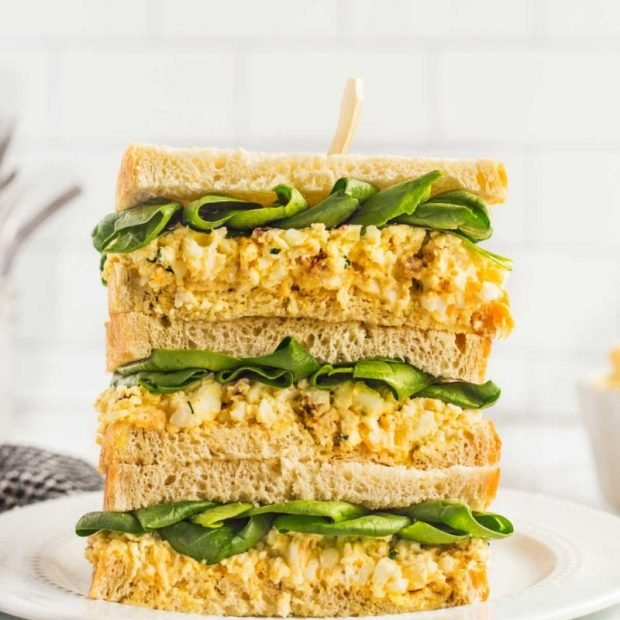 Egg Salad Sandwiches stacked on top of each other on a plate