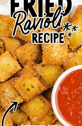 close up overhead shot of fried ravioli topped with parsley and fresh parmesan served on a plate with a cup of marinara sauce