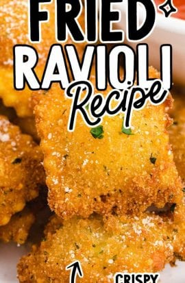 close up shot of fried ravioli topped with parsley and fresh parmesan served on a plate with a cup of marinara sauce