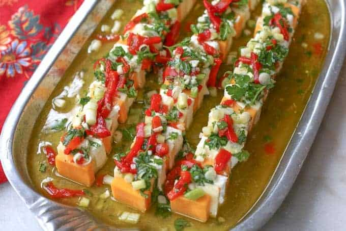 silver tray filled with marinade liquid and a mixture of cheeses topped with fresh herbs