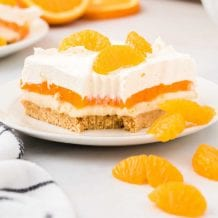 close up shot of a slice of Orange Creamsicle Lush topped with mandarin oranges on a plate