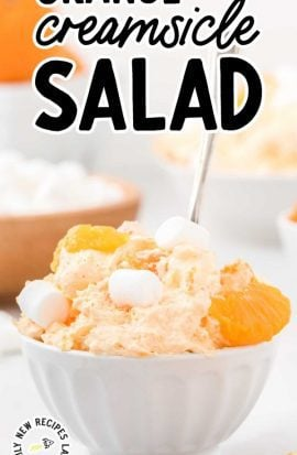 close up shot of a bowl of orange creamsicle salad topped with mandarin oranges and mini marshmallows