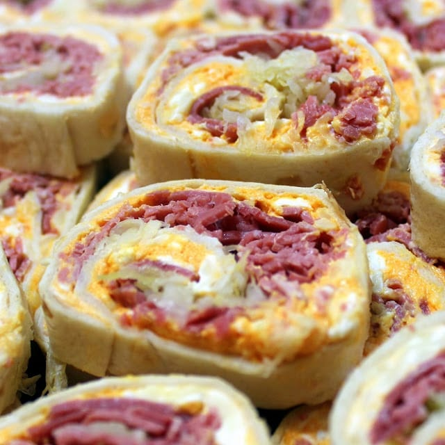 tortillas filled with cream cheese, corned beed, sauerkraut, and Russian dressing rolled up and sliced then placed on a platter on top of each other