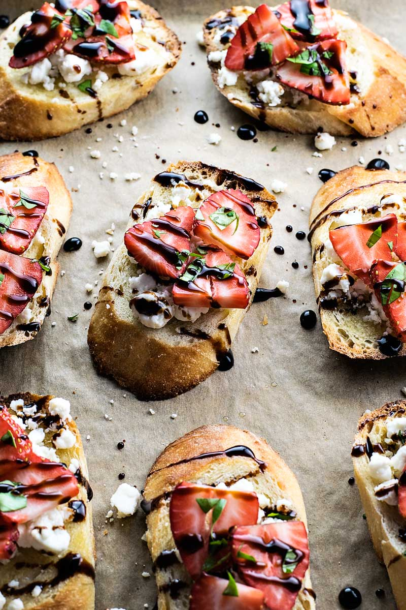 ovals of toast with cheese, strawberries and glaze drizzled on top.