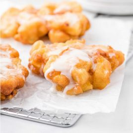 close up shot of apple fritter recipe topped with a glaze on a cooling rack